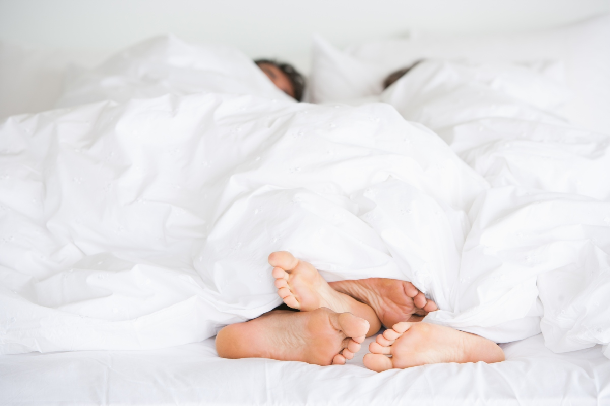 couple's feet in white bed