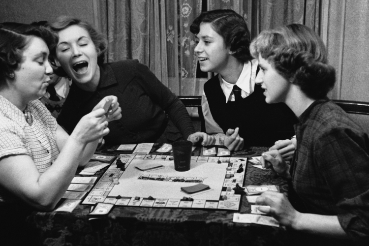 Black and white photo of actress Veronica Hurst (second from left) playing Monopoly with family members.