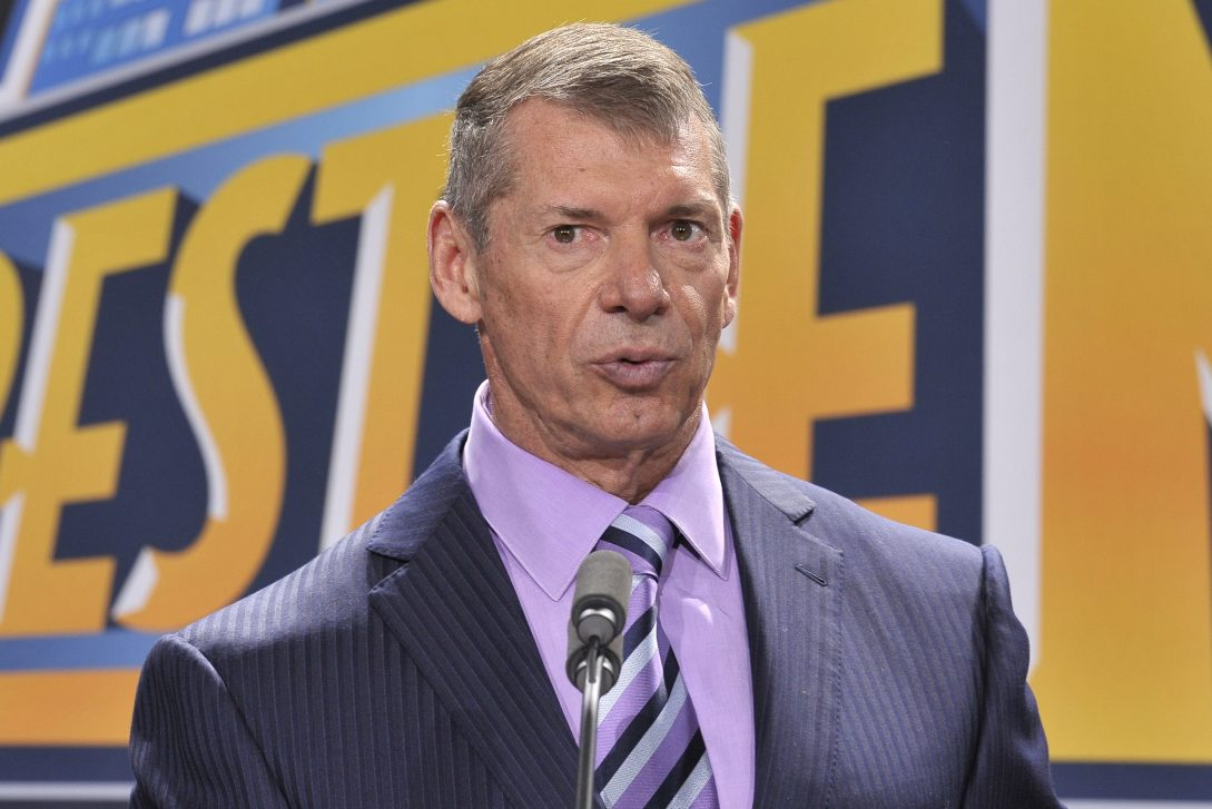 WWE CEO Vince McMahon in a suit with a purple shirt and striped tie