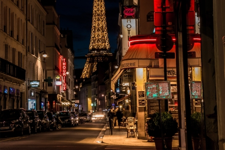 The corner of a street in Paris at night with a view of the Eiffel Tower in the background