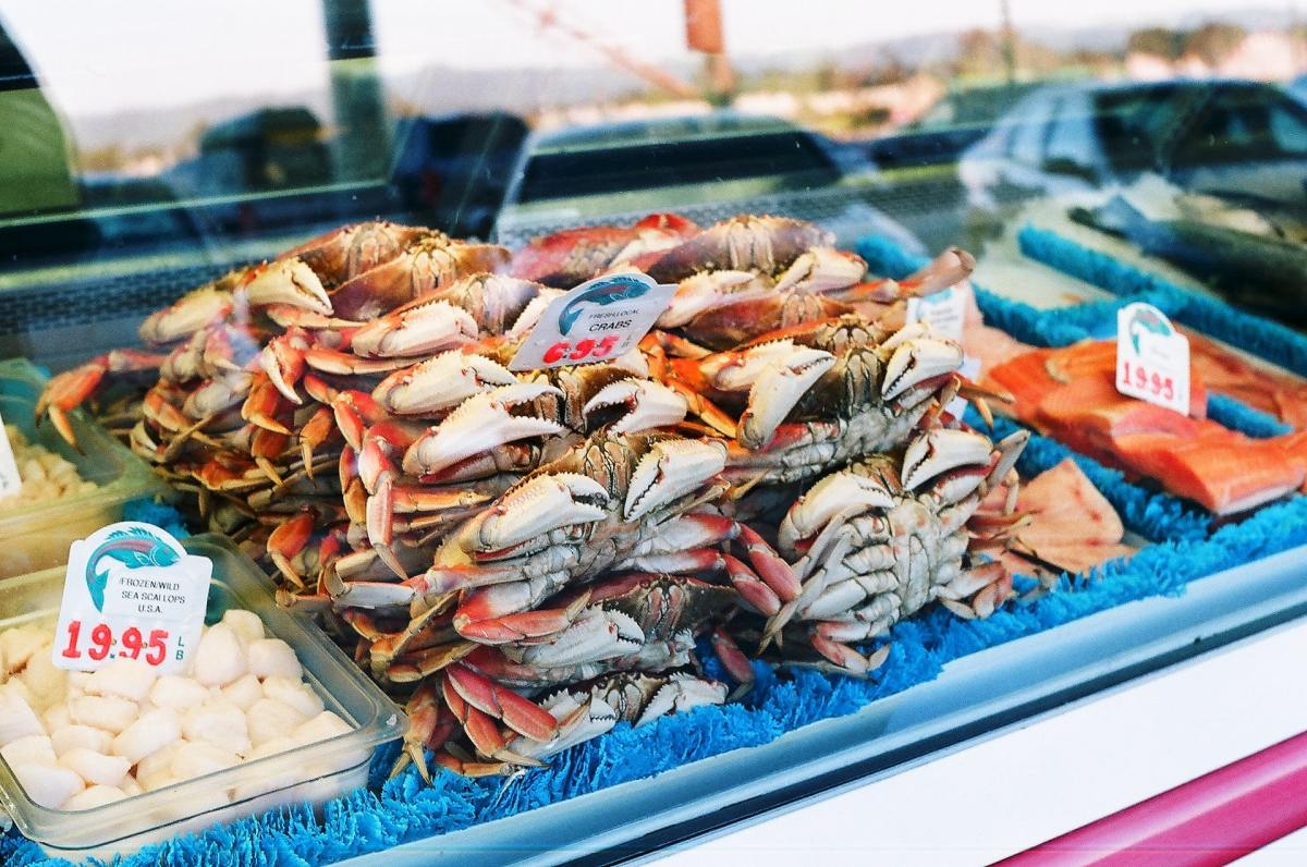 A pile of crabs sitting behind glass at a seafood market