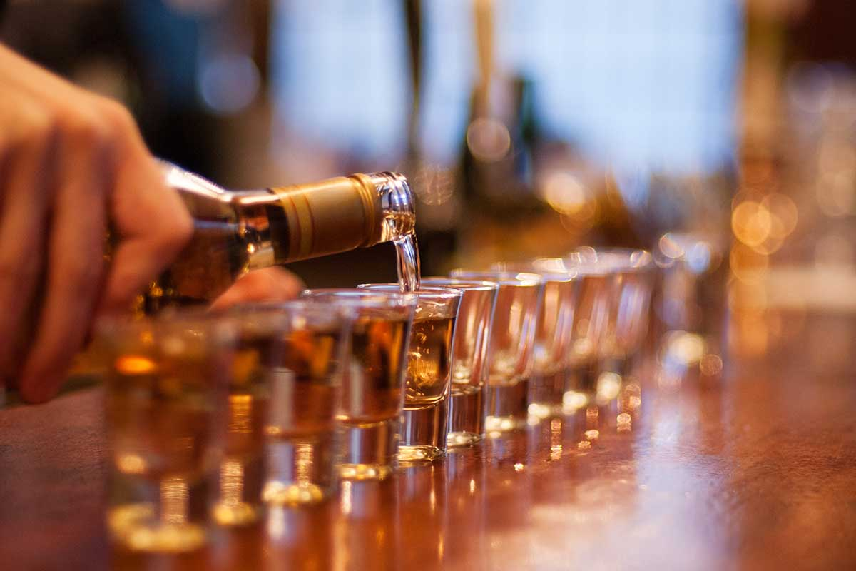 Alcohol being poured into a line of shot glasses set up on a bar