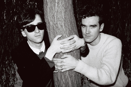 Johnny Marr (left) and Morrissey from The Smiths posed with their arms around a tree trunk in London in 1983.