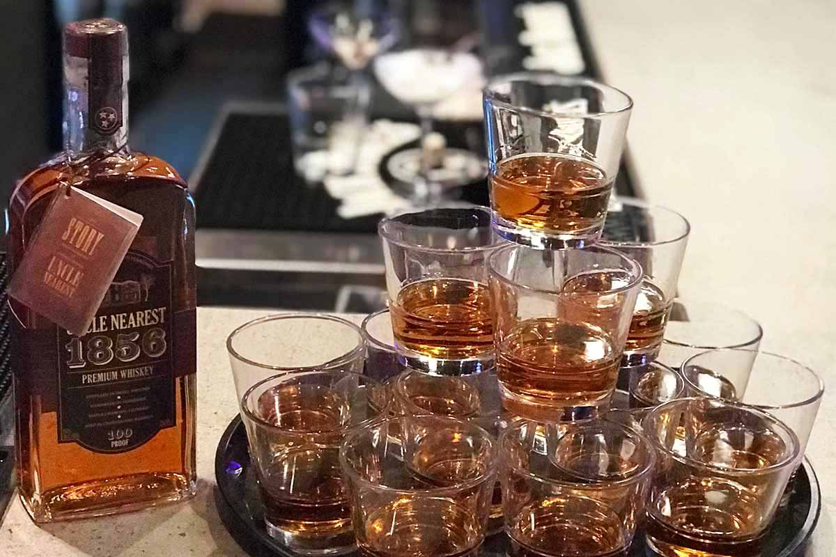 A bottle of Uncle Nearest whiskey next to a tray of glasses filled with the spirit.