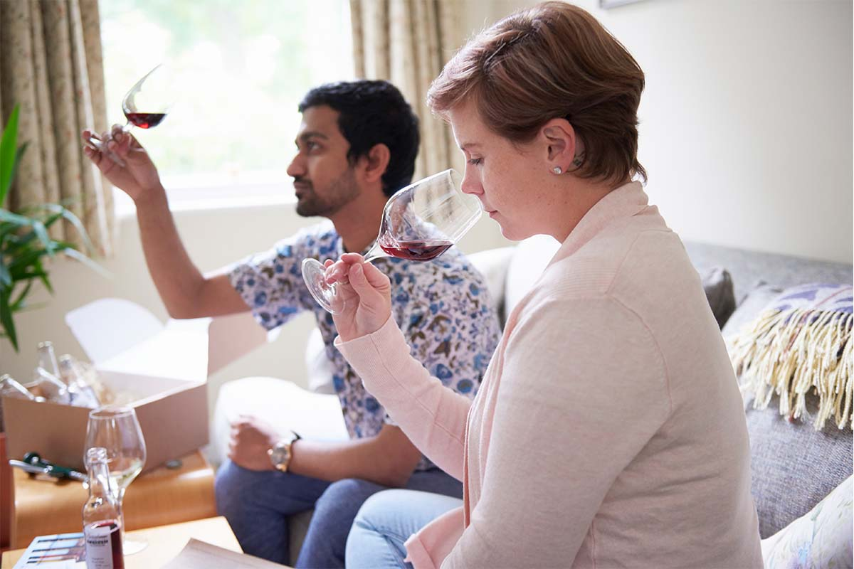 A stock image of man and woman doing wine tasting at home