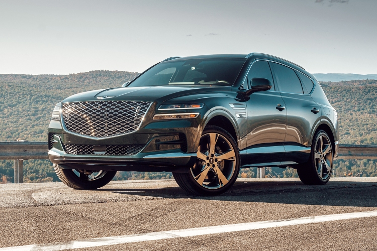 The 2021 Genesis GV80 SUV in green stands still on a road with hills behind