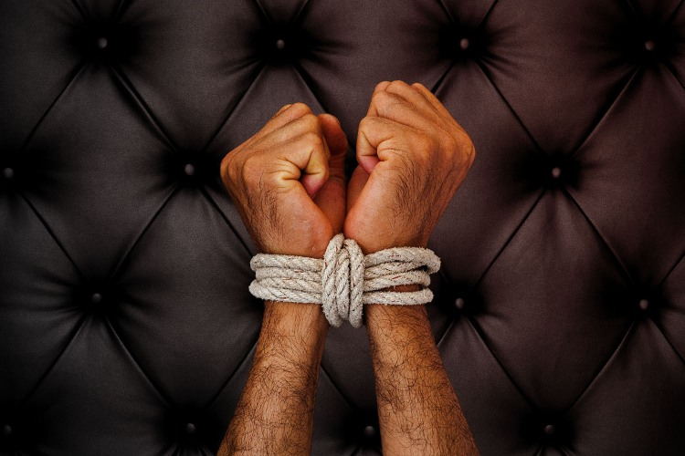 Man's wrists tied with white rope against black leather background.