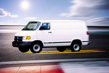 A white Dodge B-series van racing down a track with flames running behind