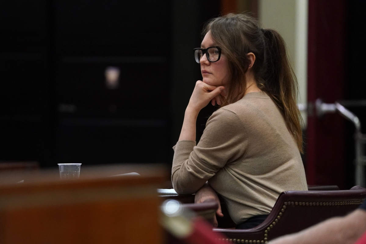 anna delvey sits in a court room resting her chin on her hand