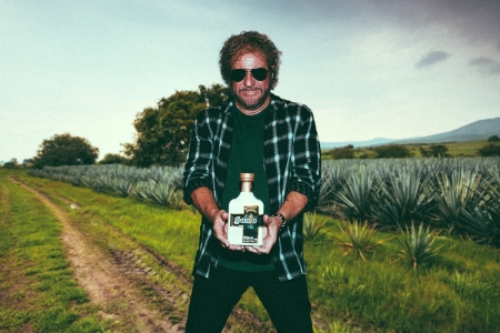 A composite image of Sammy Hagar with a bottle of this Santo tequila, superimposed on an agave field