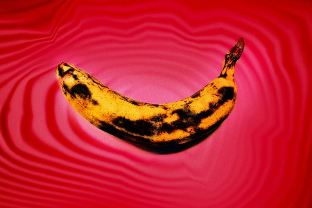 bruised banana on red background
