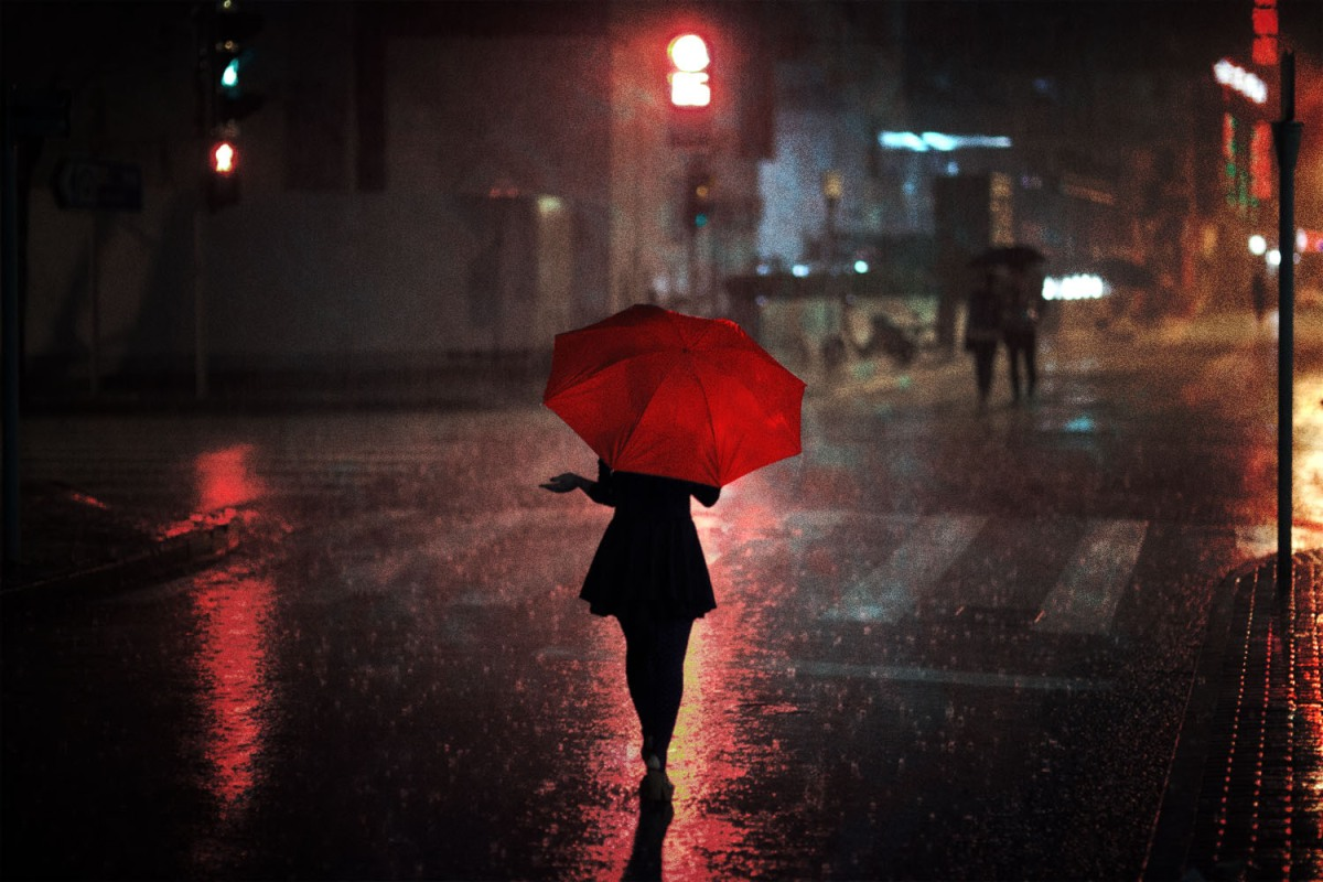 A woman in Shanghai, China appears in silhouette as she crosses a rainy street at night. She holds out her hand under a red umbrella