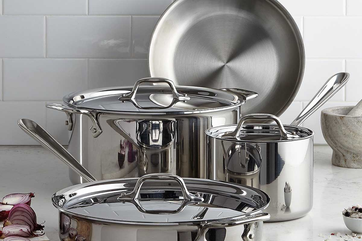 A seven-piece All-Clad Stainless Steel Cookware Set sitting on the kitchen counter