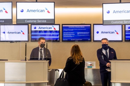 American Airlines agents check in a passenger at John Wayne Airport in Santa Ana, CA on Tuesday, January 26, 2021