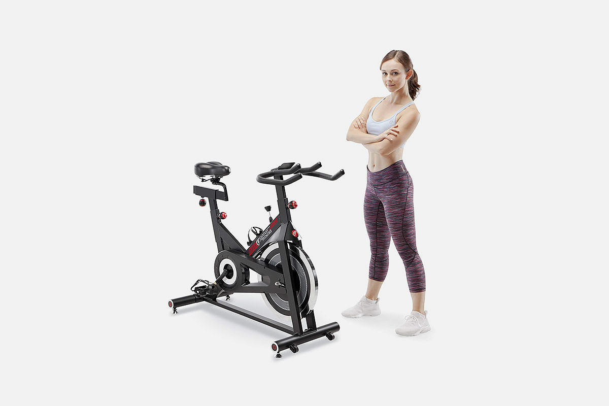 A woman in fitness gear next to a Circuit Fitness bike, which is on sale at Woot