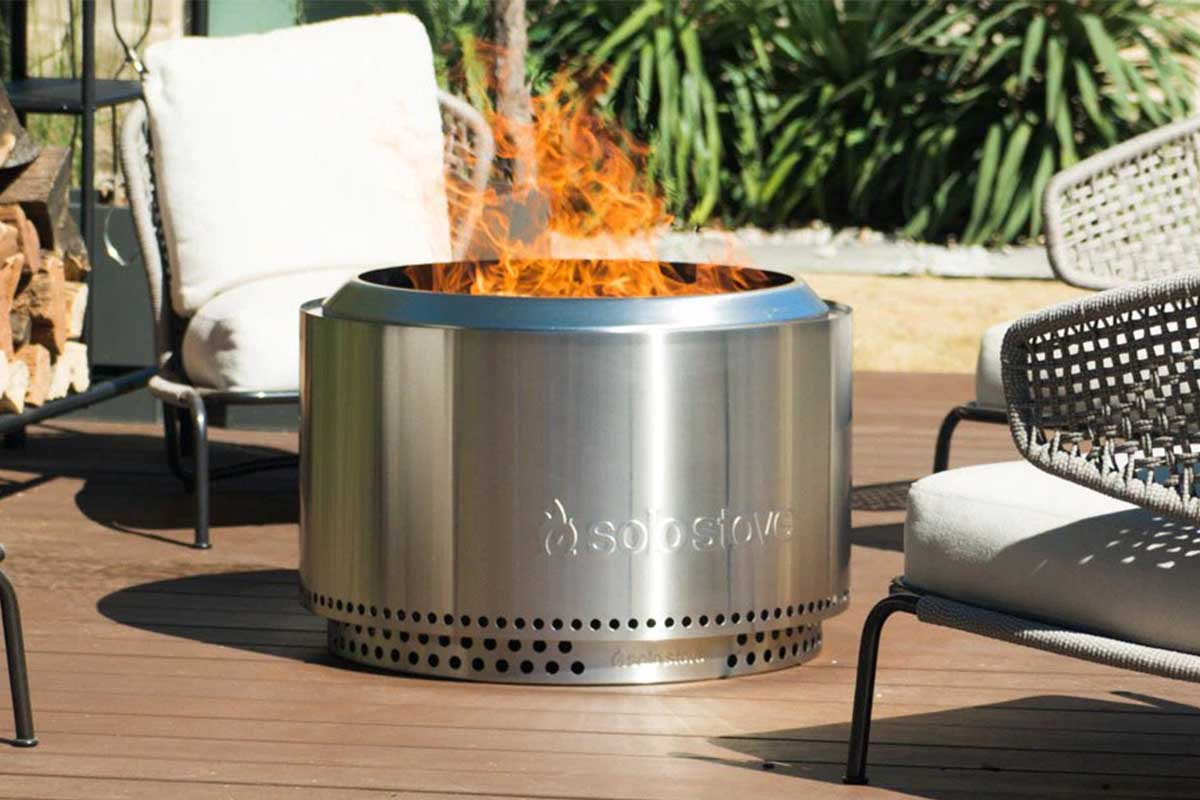 a Solo Stove fire pit in use on a back patio. The Solo Stove bundles are now on sale.