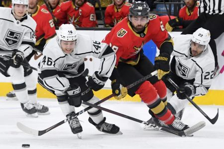 NHL players from the Los Angeles Kings and Vegas Golden Knights fight for the puck