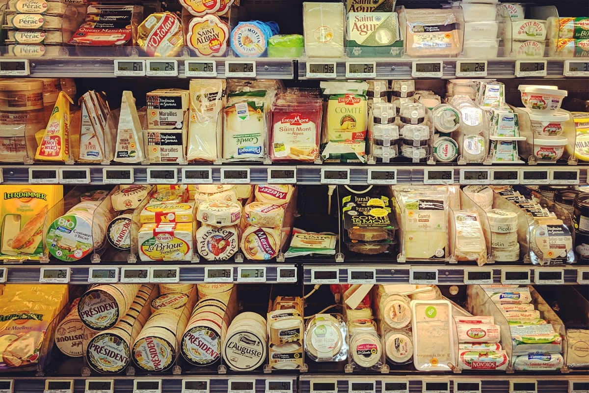A selection of cheeses at a grocery store on refrigerated shelves
