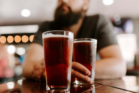 A man drinking two pints of beer. The craft beer industry showed a surprising resilience in 2020, with a net gain of craft breweries.