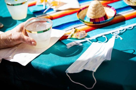 A mask is left on a table next to a margarita at Moldaw Residences in Palo Alto, Calif., on Monday, Feb. 22, 2021.