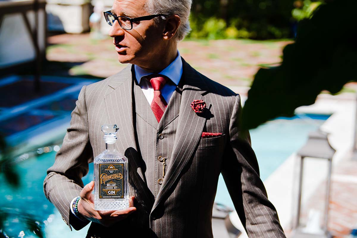 Paul Feig near a pool with a bottle of Artingstall's, his own gin brand