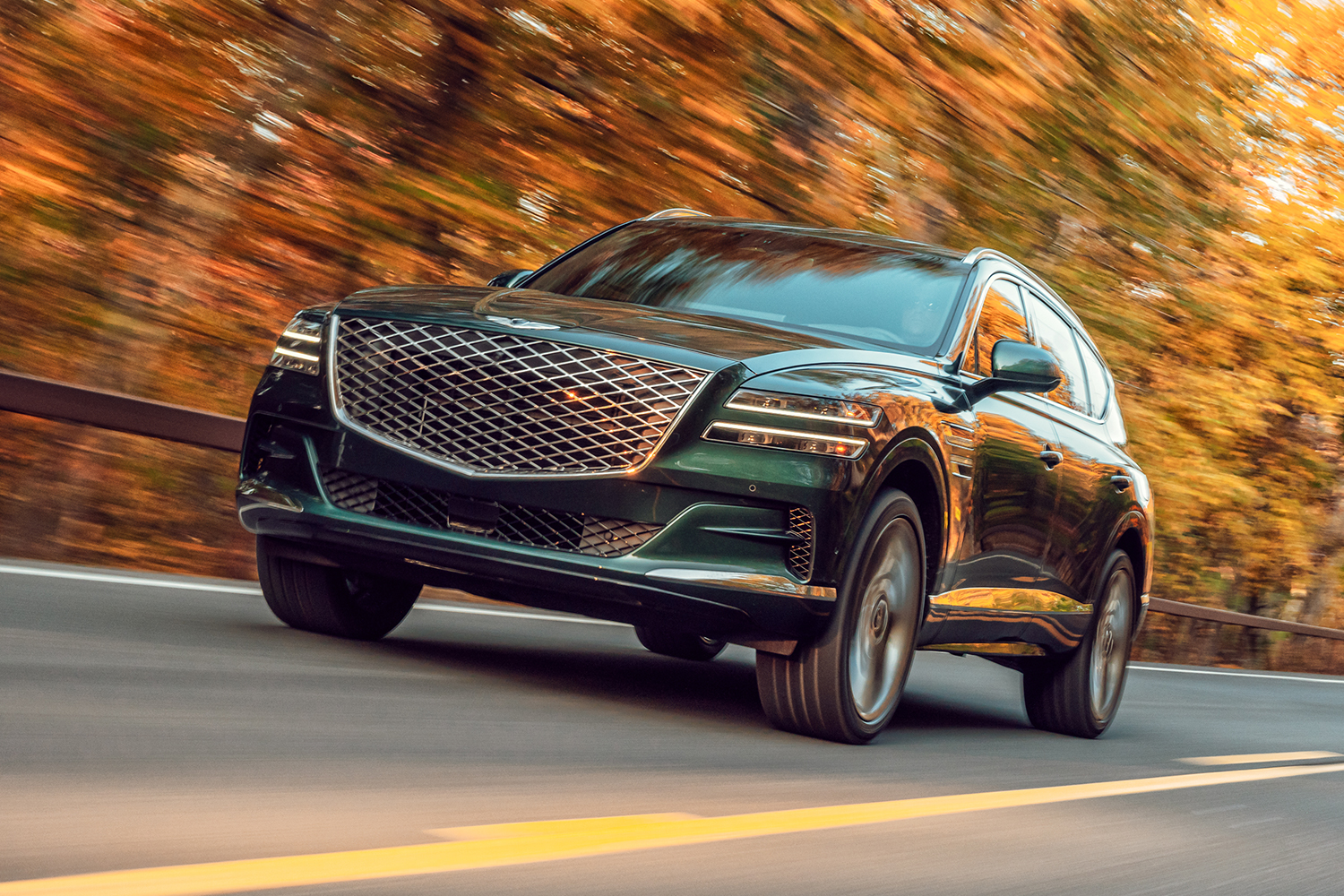 The 2021 Genesis GV80 SUV driving past trees with fall foliage
