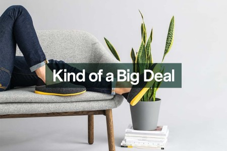 A person lying on a couch wearing mahabis slippers, now on sale at Huckberry