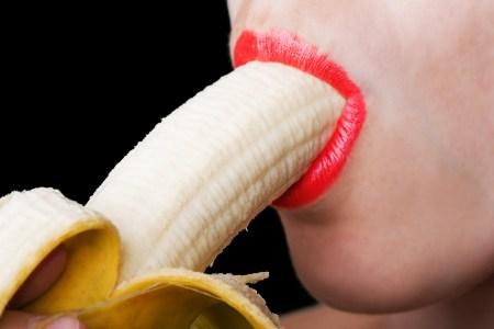 close-up of woman sucking on a banana