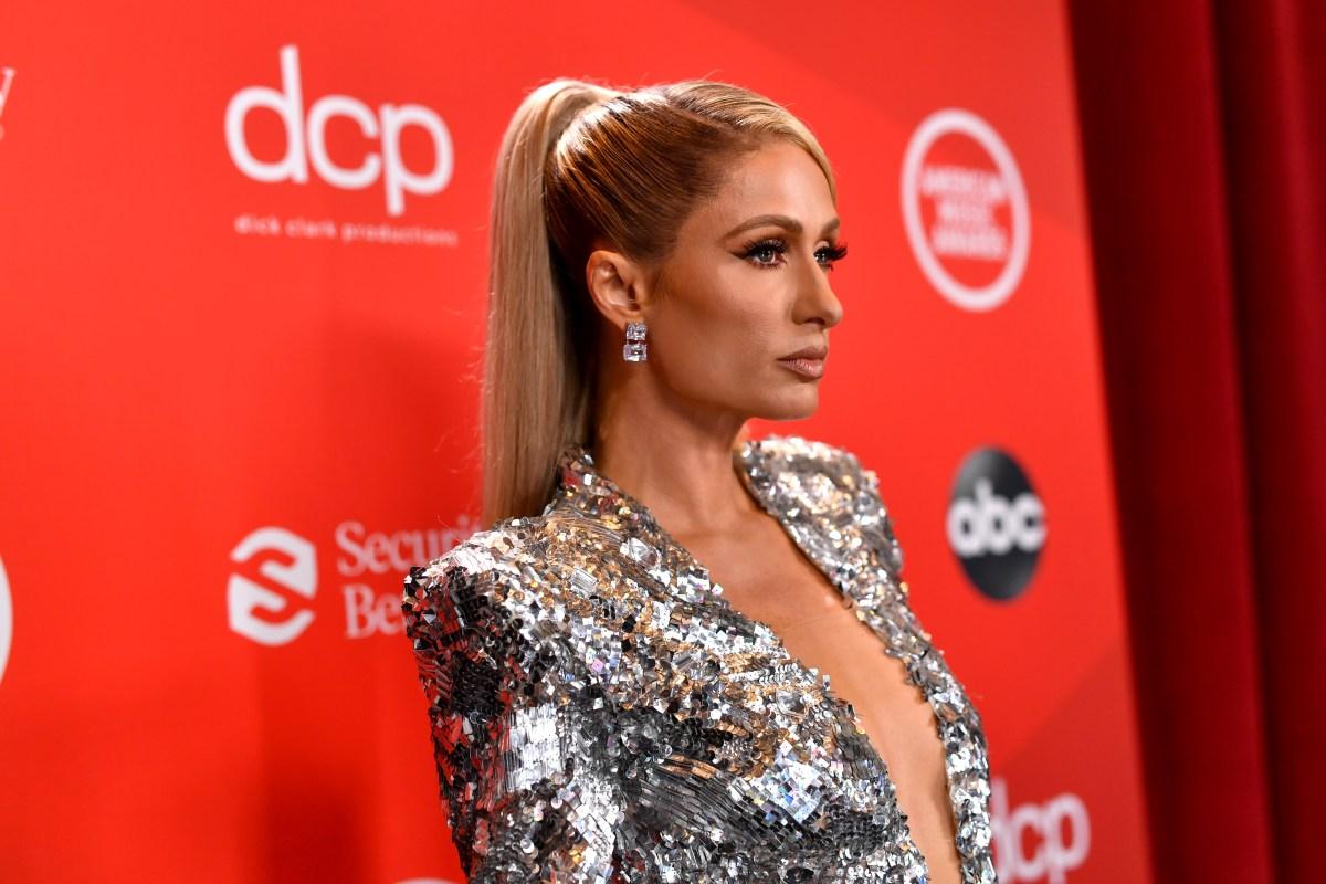 Paris Hilton posing against a red backdrop