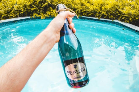 man holding bottle of prosecco with a pool in the background