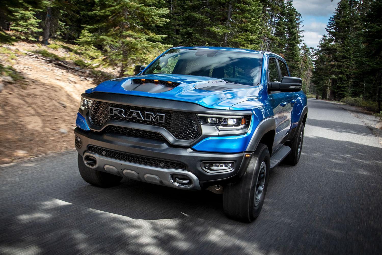 A blue 2021 Ram 1500 TRX pickup truck driving down the road