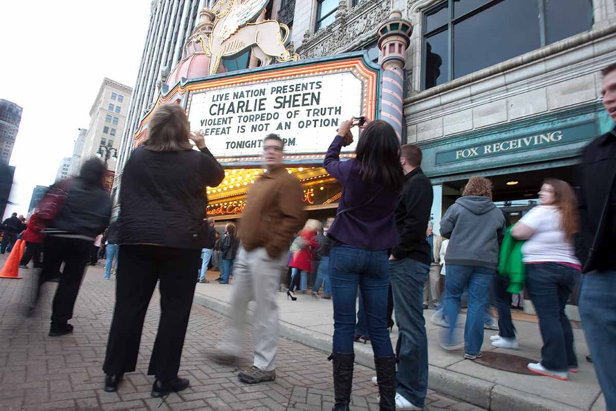 """Charlie Sheen fans pose for pictures in front of the Fox Theatre in Detroit, Michigan on April 2, 2011 to start his show """"Violent Torpedo of Truth/Defeat is Not an Option."""""""