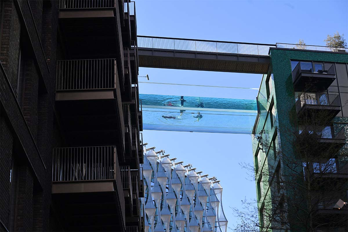 Models swim in a transparent acrylic swimming pool bridge that is fixed between two apartment blocks at Embassy Gardens next to the new US Embassy in south-west London on April 22, 2021. - A world first, the transparent 25-metre-long outdoor pool, known as the Sky Pool, will allow residents to swim from one building to the other, 10 storeys above the ground.