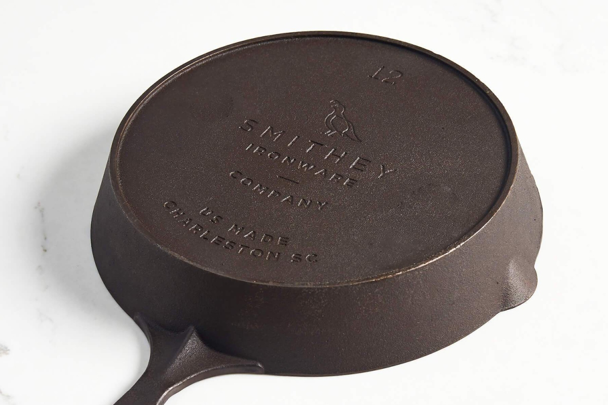 A Smithey No. 12 cast iron skillet flipped upside down on a table