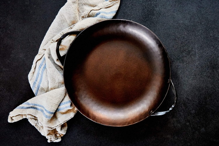 The Carbon Steel Round Roaster Pan from Smithey sitting next to a towel