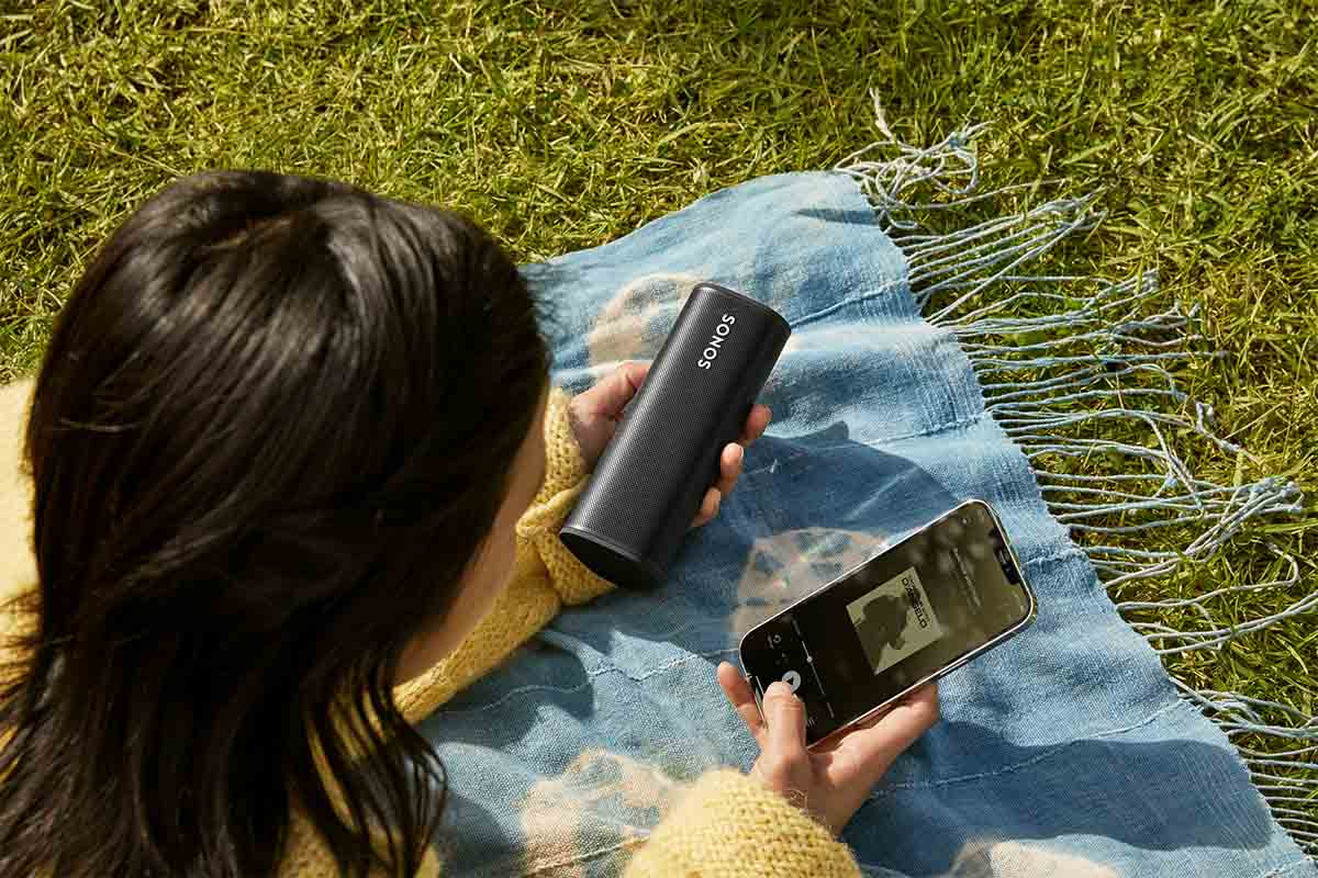 A woman pairing her phone with a Sonos Roam while sitting on a blanket in a park