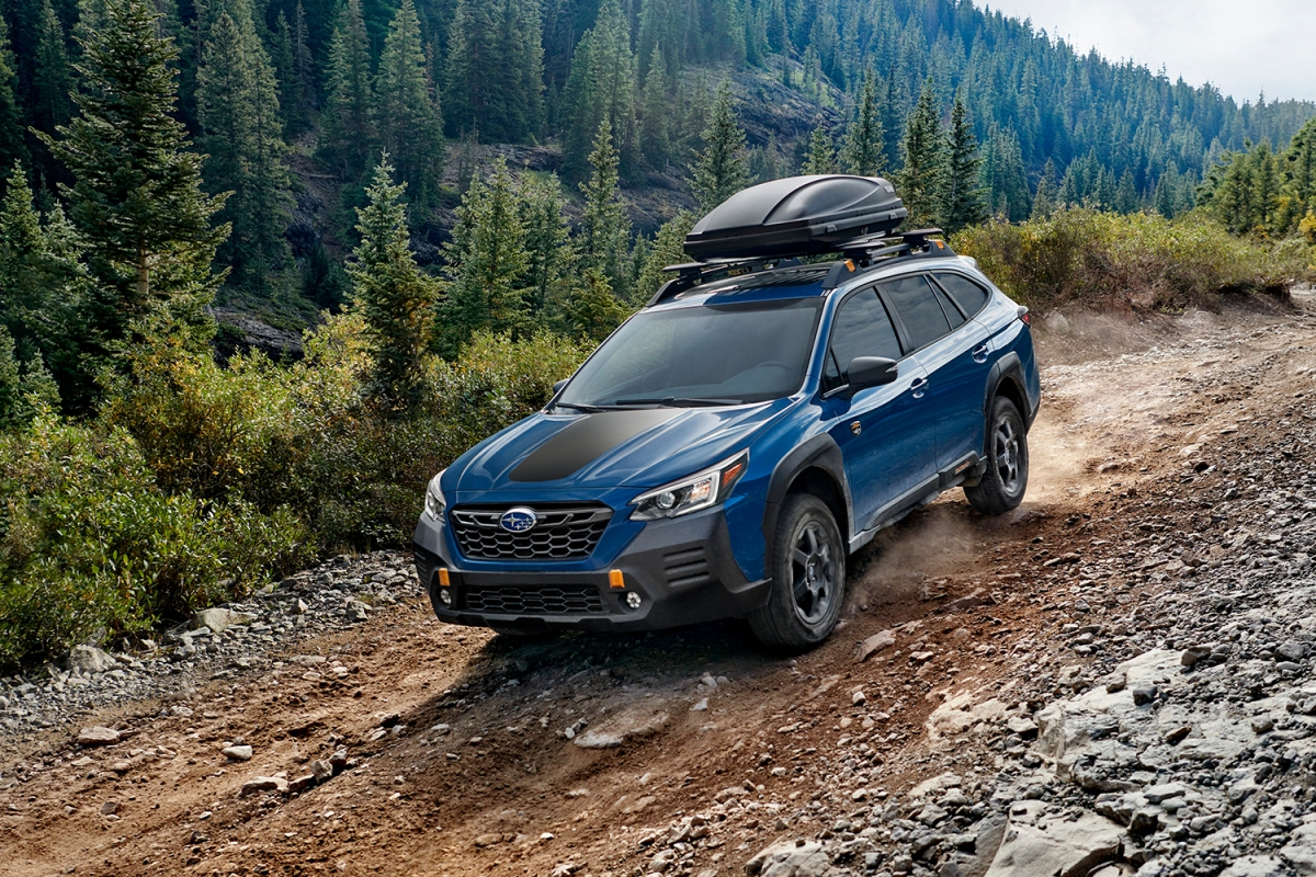 A blue 2022 Subaru Outback Wilderness SUV driving down an off-road trail