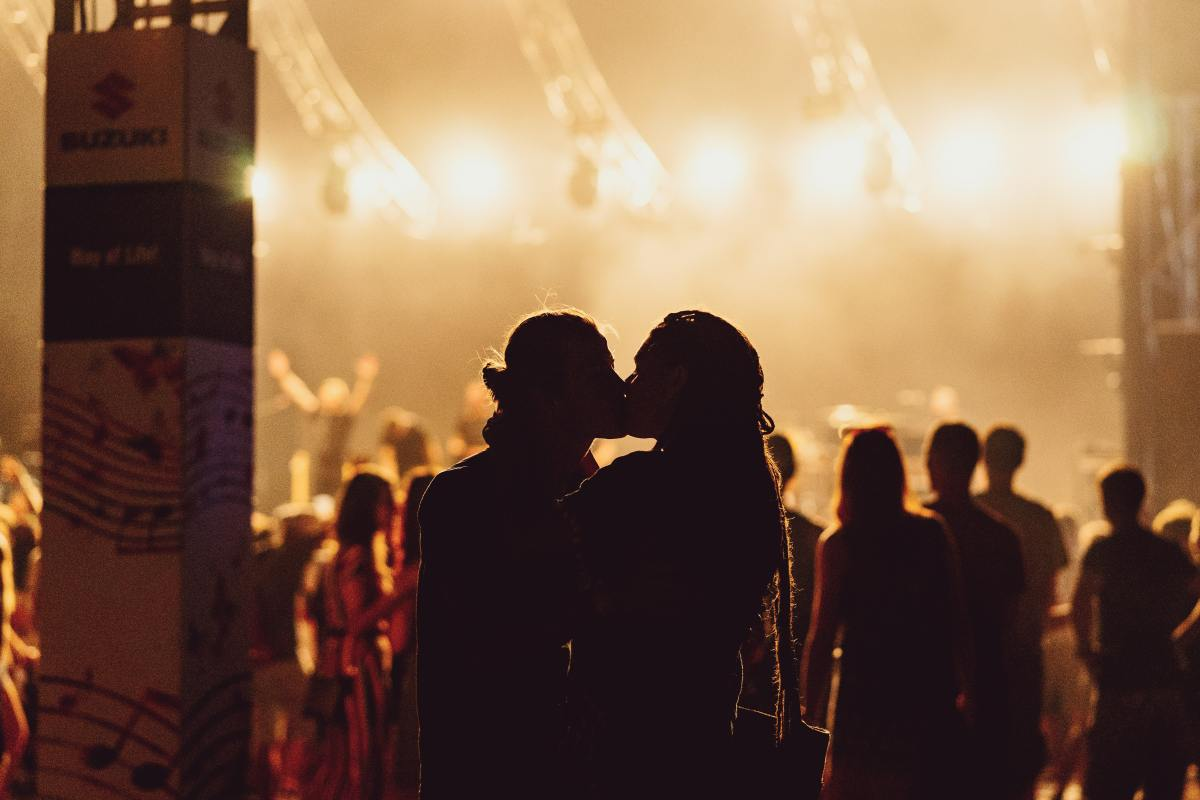 Shadowy figures of man and woman kissing during a concert
