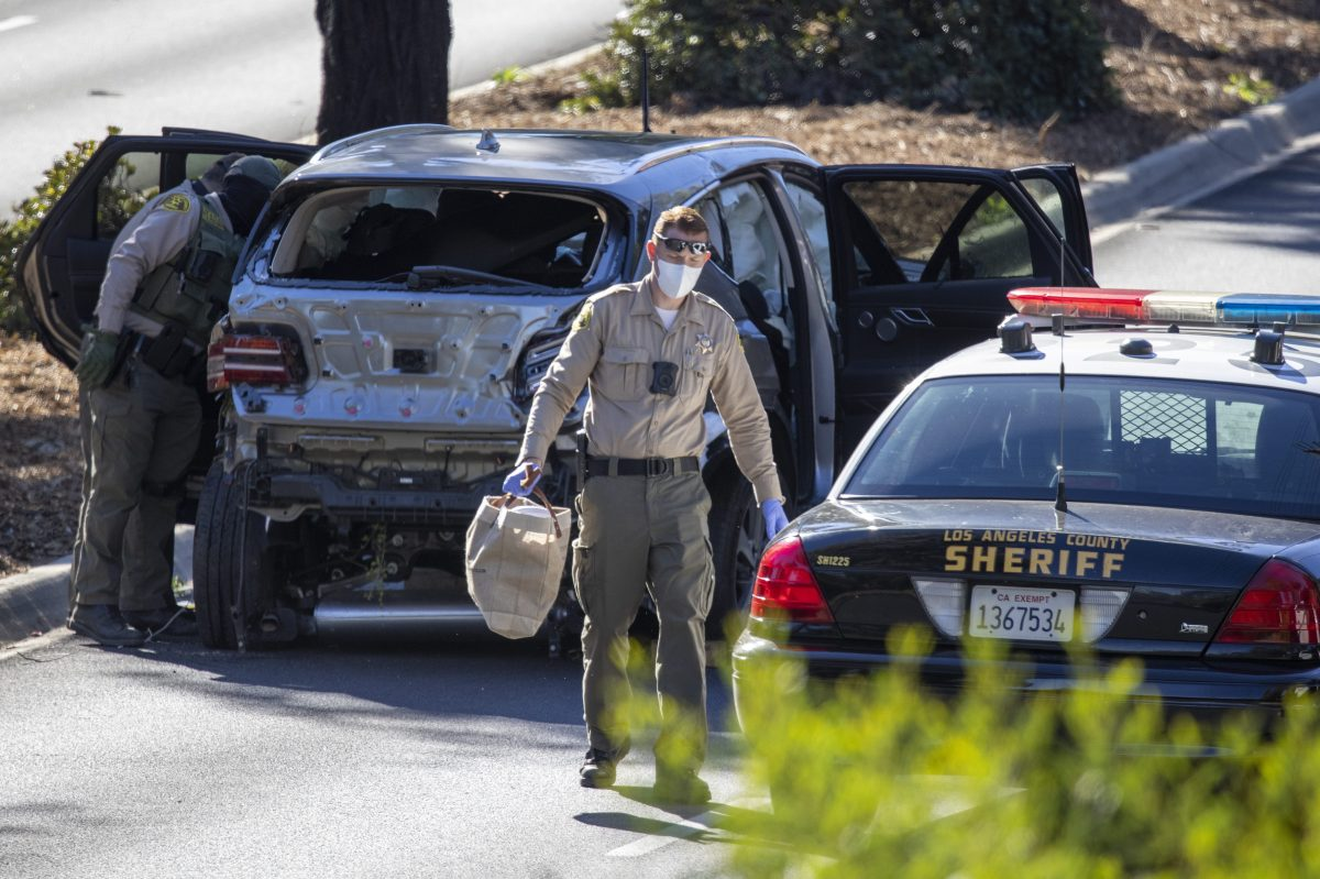 Los Angeles County Sherrif deputies with the vehicle that golf legend Tiger Woods crashed