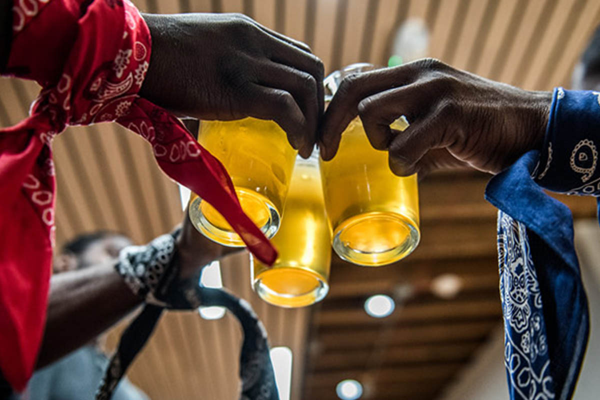 Three glasses of beer held in three hands representing three different gangs. Former gang members work together at TRU Colors in North Carolina.