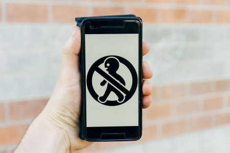 "One hand on a phone that is showing a ""do not walk"" symbol"