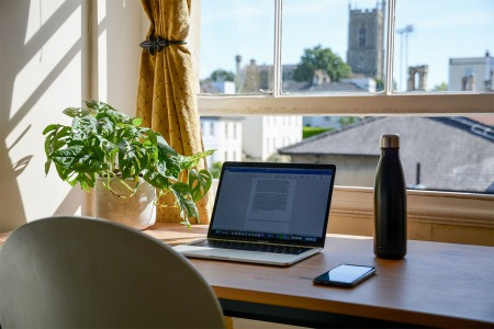 A laptop computer sitting on a desk by a window in a home