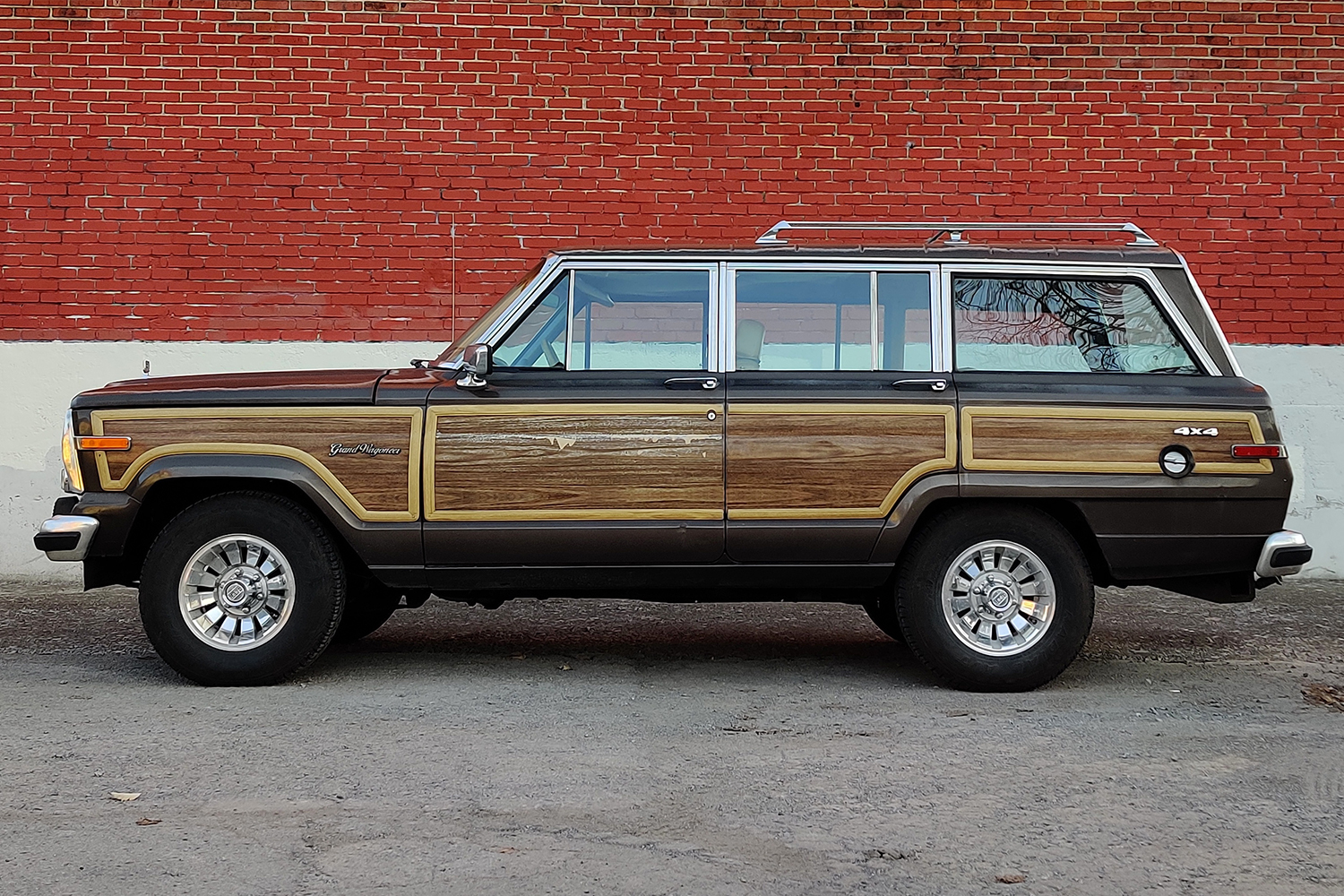 The side profile of a 1987 Jeep Grand Wagoneer against a red brick wall
