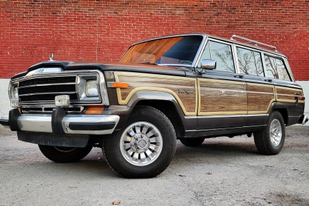 A 1987 Jeep Grand Wagoneer sitting in front of a red brick wall