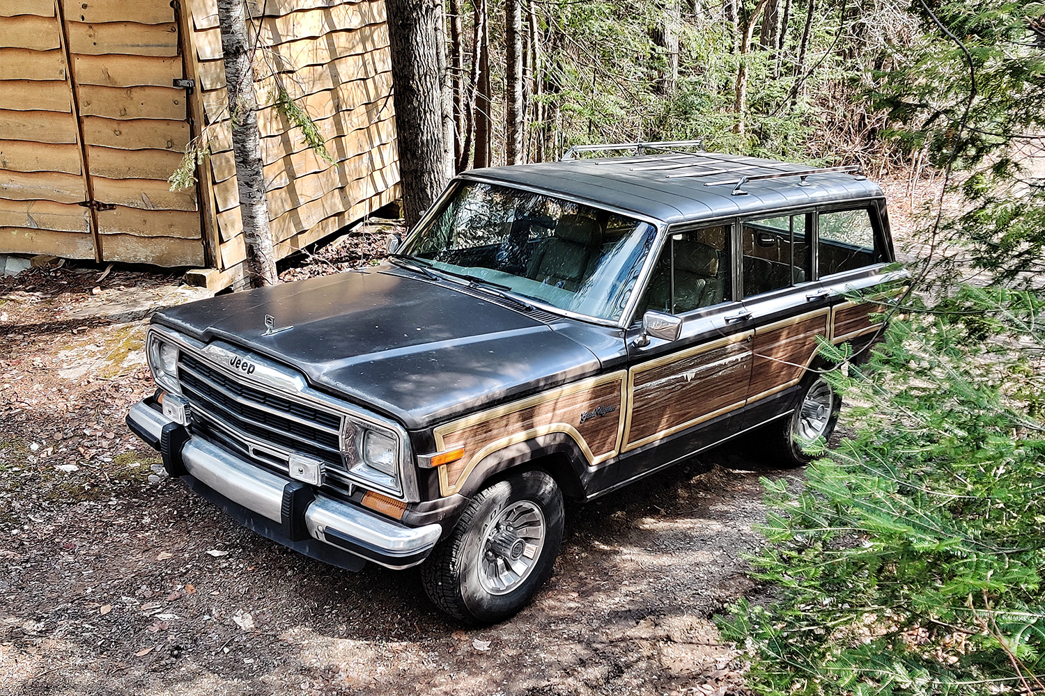 A 1987 Jeep Grand Wagoneer next to a cabin in the woods