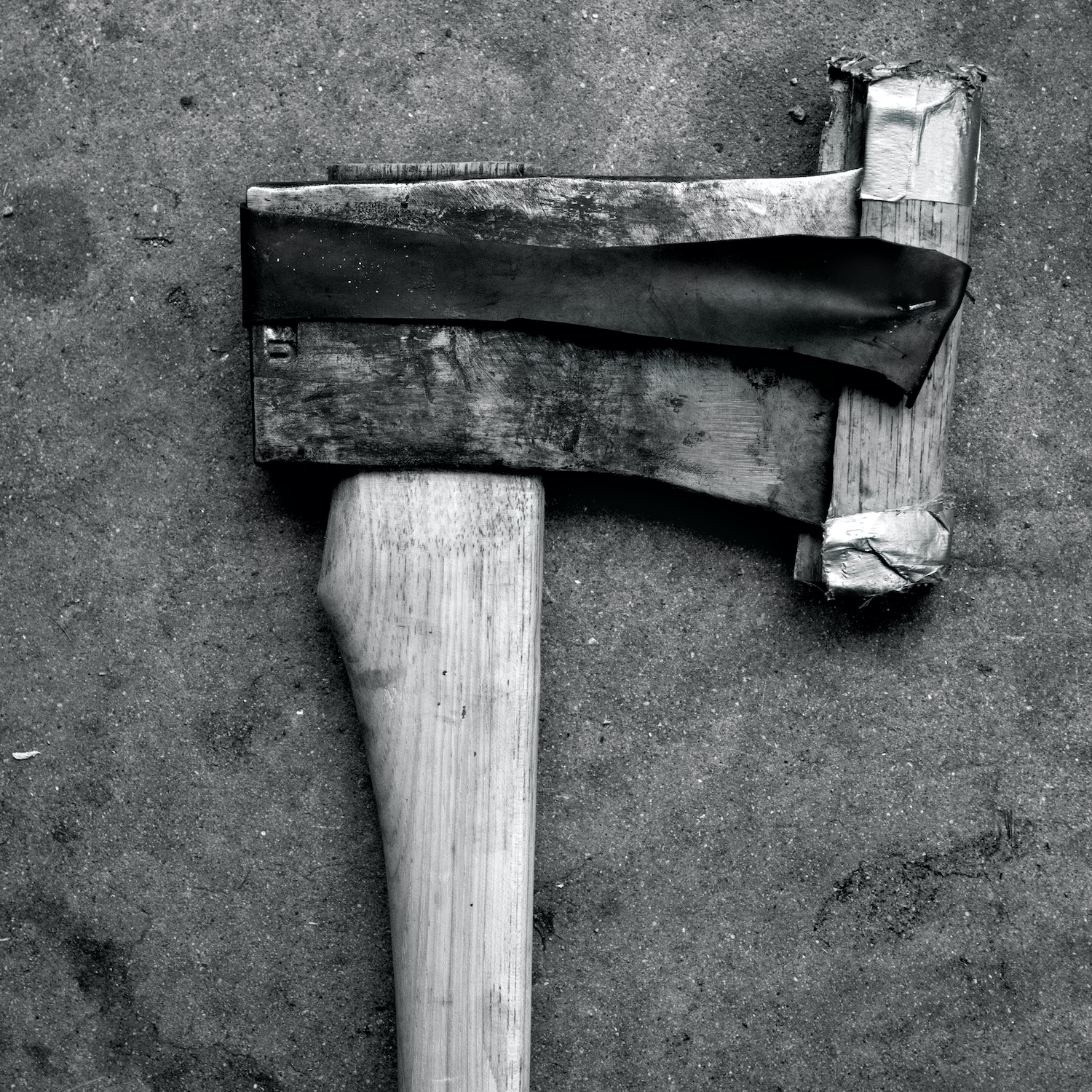 A black and white photo of a vintage axe on the ground