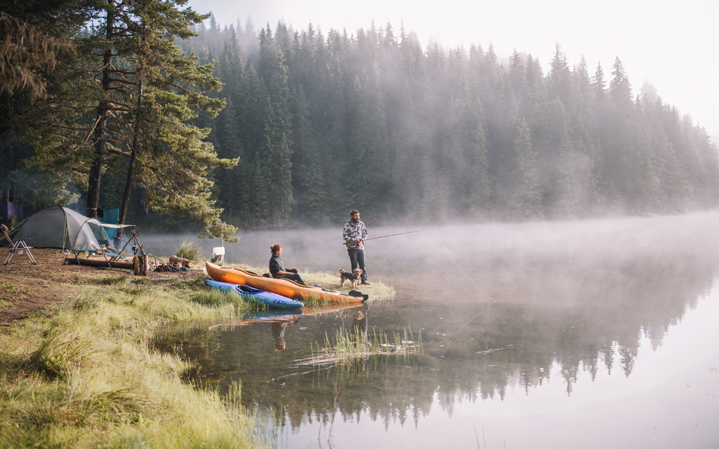 Camping Clothing with man fishing on the shore of a lake