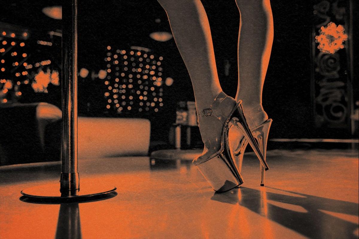 woman wearing platform heels stands near stripper pole