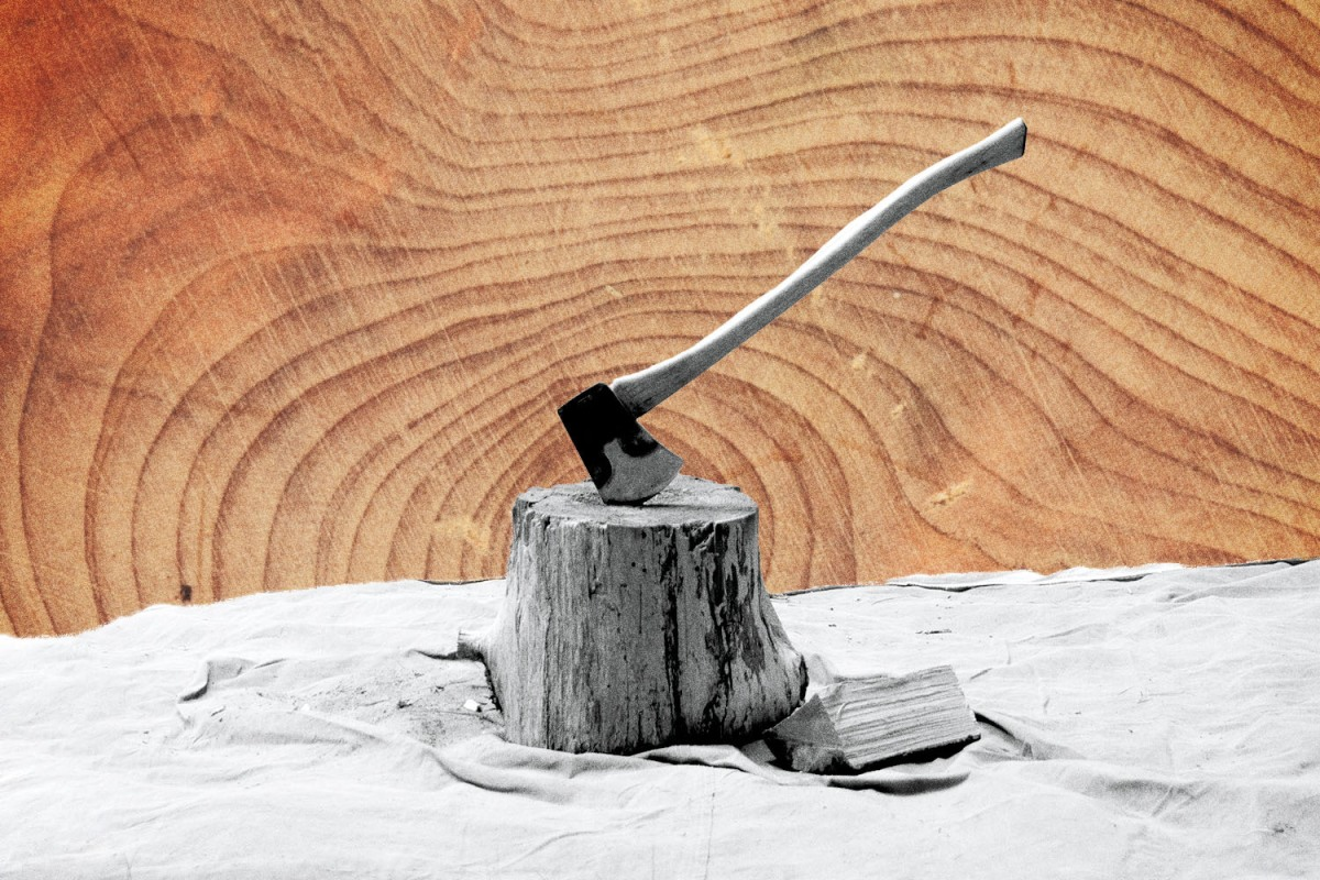 A black and white photo of an axe sticking in a wood stump with a wood-grain background