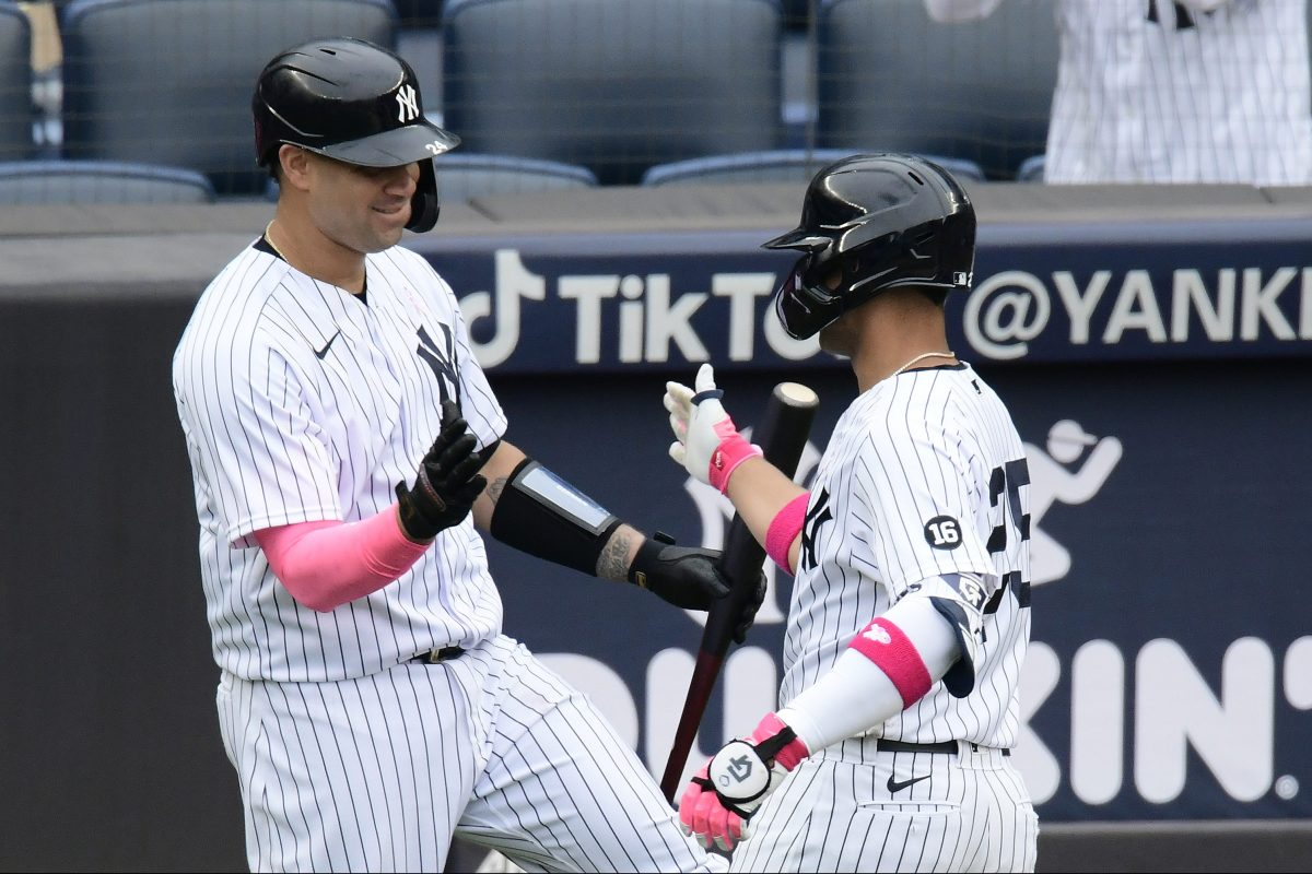 Gleyber Torres of the New York Yankees is congratulated by Gary Sanchez after hitting a solo home run against the Washington Nationals